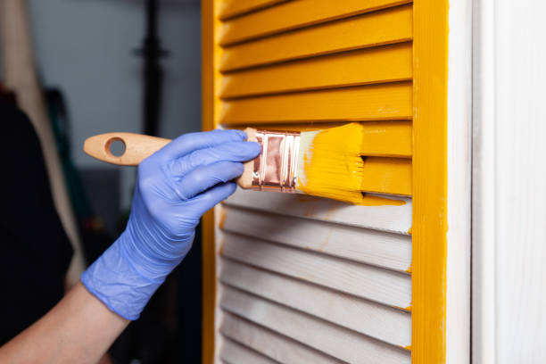 Closeup woman hand in purple rubber glove with paintbrush painting natural wooden door with yellow paint, creative design house renovation theme. How to Paint Wooden Surface. Selected focus